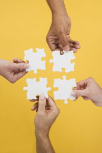 Close up of four hands holding puzzle pieces --- Image by © Royalty-Free/Corbis
